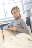 Dricka tea för ung kvinna hemma Royaltyfri Fotografi