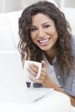Dricka Teakaffe för kvinna genom att använda bärbar datordatoren Royaltyfri Foto