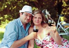 Dricka wine för par i parken Royaltyfria Bilder