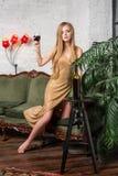 dricka winekvinna Härlig ung blond kvinna i lång guld- aftonklänning med exponeringsglas av rött vin i lyxig vind Arkivbild
