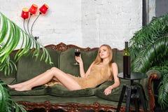 dricka winekvinna Härlig ung blond kvinna i lång guld- aftonklänning med exponeringsglas av rött vin i lyxig vind Royaltyfri Foto