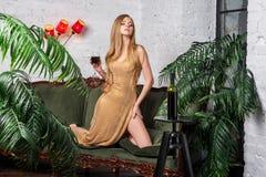 dricka winekvinna Härlig ung blond kvinna i lång guld- aftonklänning med exponeringsglas av rött vin i lyxig vind Royaltyfri Bild