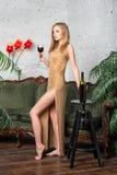 dricka winekvinna Härlig ung blond kvinna i lång guld- aftonklänning med exponeringsglas av rött vin i lyxig vind Royaltyfri Fotografi