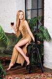 dricka winekvinna Härlig ung blond kvinna i lång guld- aftonklänning med exponeringsglas av rött vin i lyxig vind Arkivfoto