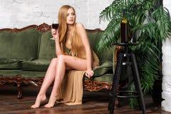 dricka winekvinna Härlig ung blond kvinna i lång guld- aftonklänning med exponeringsglas av rött vin i lyxig vind Arkivbilder