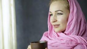 Dricker den arabiska kvinnan för härliga muslim i rosa hijab cofee framme av fönstret lager videofilmer