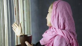 Dricker den arabiska kvinnan för härliga muslim i rosa hijab cofee framme av fönstret arkivfilmer