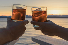 Dricker den glödande coctailen för sjösidan i handslut upp Arkivfoto