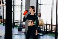 Dricker den iklädda svarta sportswearen för den slanka mörker-haired flickan vatten i idrottshallen nära sportutrustningen arkivbild