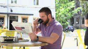 Dricker den läs- tidningen för mannen kaffe stock video