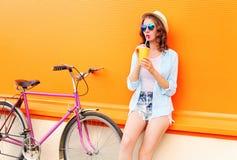 Dricker den nätta kvinnan för mode fruktfruktsaft från koppen med den retro cykeln över den färgrika apelsinen royaltyfria foton