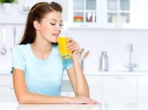 dricker den nya fruktsaftorangekvinnan Royaltyfri Foto