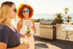 Dricker det härliga innehavet för kvinna två med leenden på deras framsidor Fotografering för Bildbyråer