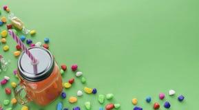 Dricker naturliga nya Smoothies för baner i den glass koppen med sugrör på grön bakgrund Royaltyfri Foto