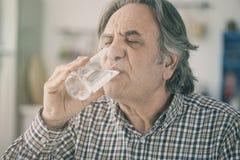 Dricksvatten för hög man från exponeringsglas i kök fotografering för bildbyråer