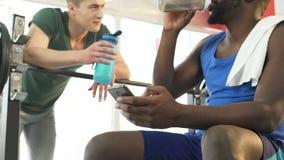 Dricksvatten för två idrotts- vänner och samtal om konkurrens på idrottshallen stock video