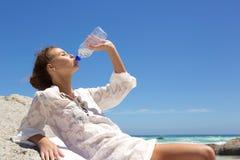 Dricksvatten för ung kvinna från flaskan på stranden Arkivbilder