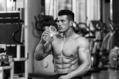 Dricksvatten för ung man från flaskan arkivfoto