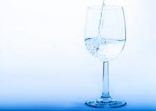 Dricksvatten hälls från en flaska in i ett exponeringsglas Royaltyfri Fotografi