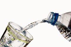 Dricksvatten hälls från en flaska in i ett exponeringsglas Royaltyfri Foto