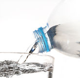 Dricksvatten hälls från en flaska in i ett exponeringsglas på vitbac Arkivbild