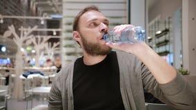dricksvatten Stilig man med ett skägg som öppnar en flaska av vattensammanträde i ett offentligt ställe Mannen är törstig stock video