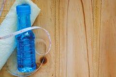 Dricksvattenflaska, handduk och måttband på trätabellen arkivfoto