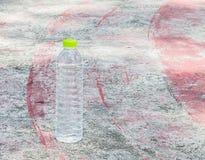 Dricksvattenflaska på gammalt golv för idrottshall för tappninggrungebetong Arkivfoton