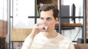 Dricksvattensammanträde för ung man på en soffa som är hemmastadd och ser kameran royaltyfri bild