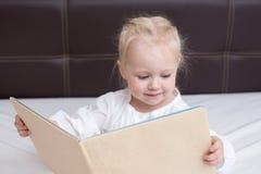 Drie éénjarigenmeisje die een boek lezen stock afbeeldingen