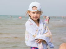 Drie éénjarigenmeisje die zich op die het strand bevinden in een handdoek wordt verpakt Royalty-vrije Stock Afbeelding