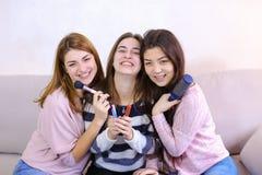 Drie aantrekkelijke jonge vrienden die met glimlachen op camera stellen en Stock Foto