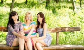 Drie aantrekkelijke meisjes op een houten bank stock afbeelding