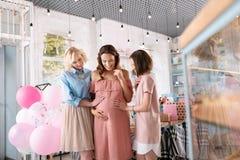 Drie aantrekkelijke vrouwen die elkaar in aardige moderne koffie ontmoeten royalty-vrije stock fotografie