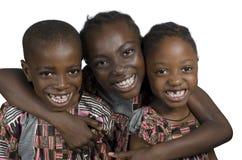 Drie Afrikaanse jonge geitjes die bij een andere het glimlachen houden Royalty-vrije Stock Afbeelding