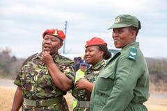 Drie Afrikaanse vrouwenambtenaar in rode baret en groene eenvormig van de Defensiekracht USDF van Umbutfo Swasiland royalty-vrije stock foto's
