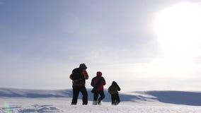 drie alpinisttoeristen volgen elkaar in de sneeuwwoestijn Het teamwerk en overwinning het team van bedrijfsmensen gaat aan stock video