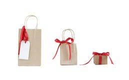 Drie ambachtdocument pakketten met rode linten - isol Stock Fotografie