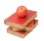 Drie antieke boeken en appel stock afbeelding