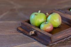 Drie appelen in een houten doos stock afbeelding