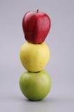 Drie appelen op een grijze achtergrond Stock Fotografie
