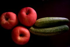 Drie appelen, twee komkommers op het schot stock fotografie