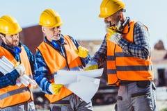 Drie arbeiders in eenvormige onderzoekende de bouwplannen en het spreken op draagbare radio stock fotografie
