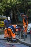 Drie arbeiders gehamerde kolommen dichtbij de stoep royalty-vrije stock afbeelding