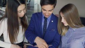 Drie arbeiders kijken aan het digitale tabletscherm binnen bureau Knappe mens, die gadget houden stock footage