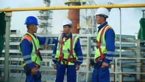 Drie arbeiders in productie-installatie als team die, industriële scène op achtergrond bespreken stock footage