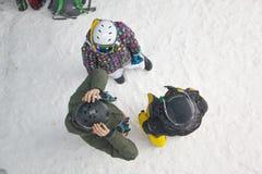Drie atleten bevinden zich alvorens op een snowboard te beginnen Stock Foto