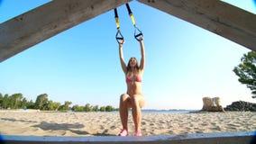 Drie atletische, sexy jonge vrouwen in zwempakken, instructeurs, die oefeningen met geschiktheids trx systeem doen, TRX-opschorti stock video