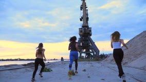 Drie atletische vrouwen in bovenkledij stoten langs de zandpijler aan van de ladingshaven, in de schemering van de ochtend stock video