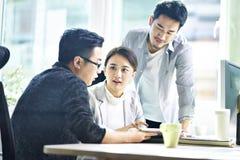Drie Aziatische collectieve stafmedewerkers die in bureau samenkomen royalty-vrije stock afbeelding